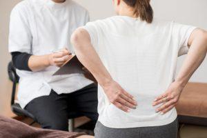腰痛の問診を受ける女性